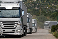 Silver trucks convoy. Caravan of silver trucks approacinh at perspectyve to viewer Stock Image