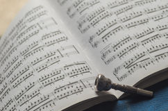 Silver Trumpet mouthpiece on sheet music book. A silver trumpet mouthpiece on sheet music book Stock Photo