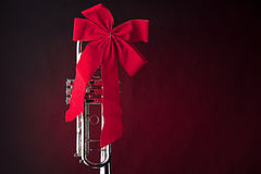 Silver Trumpet with Red Bow on Red. A silver trumpet present with a red bow isolated against a spotlight red background Royalty Free Stock Images