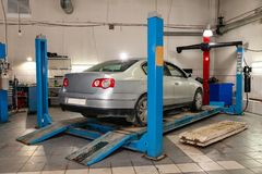 Silver used car stands on the stand wheel alignment convergence of the car in the workshop for repair of vehicles. Auto service stock photos
