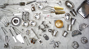 Silver utensils. Photo closeup of different variety diversified rich assortment of vintage shiny silver flatware cutlery utensils lying on tablecloth on white Stock Photos