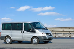 Silver van on road with blue horizon. On the background stock photos