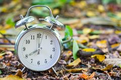 Silver vintage alarm clock on the ground with nature blurred. Silver vintage alarm clock on the ground with nature blurred background and copy space stock image