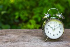 Silver vintage alarm clock on wooden table with nature blurred. Silver vintage alarm clock on wooden table with nature blurred background and copy space stock photo