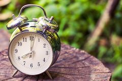 Silver vintage alarm clock on wooden table with nature blurred. Silver vintage alarm clock show 8 o`clock on wooden table with nature blurred background and stock photos