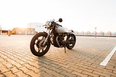 Silver vintage custom motorcycle cafe racer. Brutal custom vintage motorbike cafe racer motorcycle with raw metal gas tank and tape cross over optic at headlamp royalty free stock photo