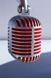 Silver vintage microphone with red membrane сlose up. On a grey background royalty free stock photo
