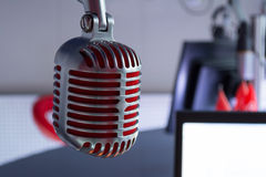 Silver vintage microphone with red membrane сlose up. On a grey background stock images