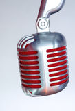 Silver vintage microphone with red membrane on a grey vintage background. Silver vintage microphone with red membrane сlose up on a grey vintage background stock photos