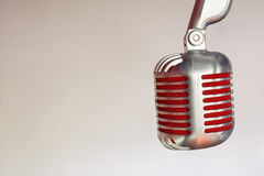 Silver vintage microphone with red membrane on a grey vintage background. Silver vintage microphone with red membrane сlose up on a grey vintage background royalty free stock photo