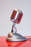 Silver vintage microphone with red membrane on a red table Royalty Free Stock Images