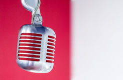 Silver vintage microphone with red membrane on a red white background. Silver vintage microphone with red membrane on a red-white background stock photos