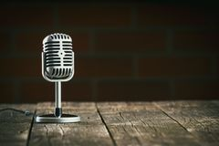 Silver vintage microphone. Silver vintage microphone on old wooden table stock images