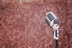 Silver vintage microphone in the studio on rusty texture background Royalty Free Stock Images