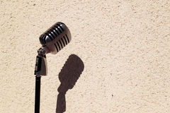 Silver vintage microphone in the studio on wall background Stock Images