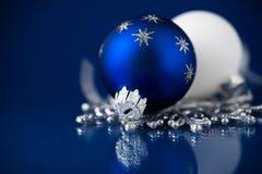 Silver-, vit- och blåttjulprydnader på mörker - blå bakgrund Glad julkort Arkivfoton