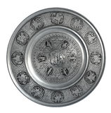 Silver wall plate Adam and Eve. Silver colored pewter decorative plate Adam and Eve in the Garden of Eden isolated on a white background Royalty Free Stock Image