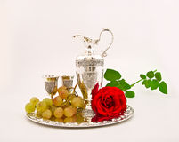 Silver ware - a jug and glasses and grapes Royalty Free Stock Images