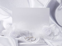 Silver wedding rings and card. Silver wedding rings, card, flowers from silk on white fabric Royalty Free Stock Photos