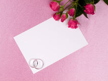 Silver wedding rings, card and roses stock images