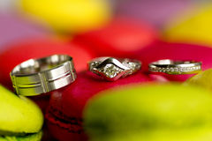 Silver wedding rings and engagement ring on macaroon Royalty Free Stock Image