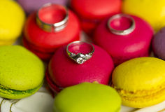 Silver wedding rings and engagement ring on macaroon Stock Photography