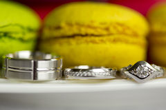 Silver wedding rings and engagement ring and macaroon Stock Images