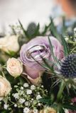 Silver wedding rings on flower bouquet Stock Photo