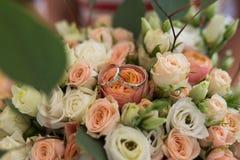 Silver wedding rings lie in a bud of orange rose. Wedding rings lie on a flower bud royalty free stock image