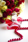 Silver wedding rings with perfume bottle and wedding bouquet of red and white roses Royalty Free Stock Photo