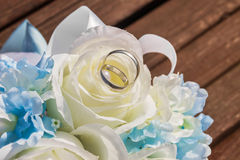 Silver wedding rings are on petals of artificial rose Stock Images