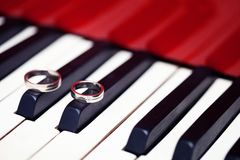 Silver wedding rings at the piano keyboard Royalty Free Stock Images