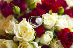 Silver wedding rings on wedding bouquet of red and white roses. And green buds, pearls for bride and groom Stock Photos