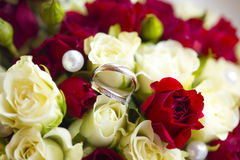Silver wedding rings on wedding bouquet. Of white and red roses, flowers and pearls Royalty Free Stock Photos