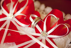 Silver wedding rings on red and white ribbons Royalty Free Stock Photography