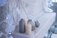 Silver and white candles and silver apples on a white piano. New year interior stock photography