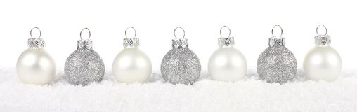 Silver and white Christmas bauble border in snow over white Royalty Free Stock Photos