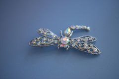silver, white gold, platinum dragonfly brooch on a blue suede leather cloth stock images