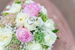 Wedding rings on bright flower bouquet royalty free stock photography