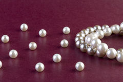 Silver and White pearls necklace on dark red Royalty Free Stock Image