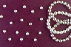 Silver and White pearls necklace on dark red Stock Photo