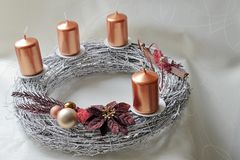 Silver wicker-work advent wreath with bronze coloured candles and christmass decoration. Placed on creamy white dinner-cloth Royalty Free Stock Photography