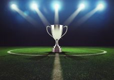 Silver winner`s cup in the middle of a soccer field Royalty Free Stock Images