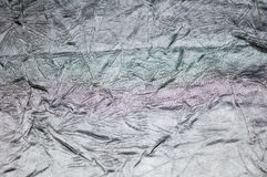 Silver wrinkled sheet metal is light, abstract images. Stock Images