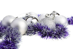 Silver Xmas balls and purple tinsel. Isolated stock photography