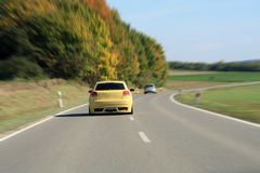 Silver and yellow car driving on the road Stock Images