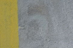 Silver and yellow paint background. Rough concrete wall painted in two unequal areas of yellow and silver color Stock Image
