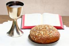 Silverbägare, öppen bibel och bröd Arkivbilder