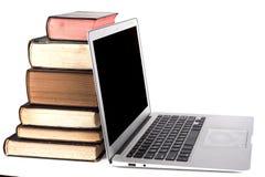 Silverbärbar dator och böcker Royaltyfri Fotografi