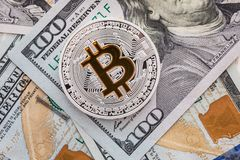 Silverbitcoin ligger på 100 dollarräkningar Bitcoin på dollarbakgrund Arkivfoton